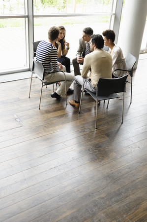 round chairs: Business people talking in office LANG_EVOIMAGES