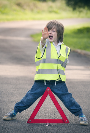 warned: Boy playing traffic worker on rural road LANG_EVOIMAGES