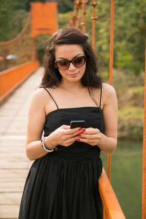 differential: Woman using smartphone on bridge LANG_EVOIMAGES
