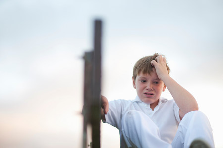 level playing field: Boy on bleachers at cricket pitch scratching head