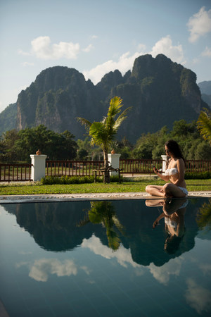 Woman sitting on poolside,Vang Vieng,Laos