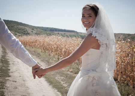 mujeres de espalda: Newlywed couple walking outdoors LANG_EVOIMAGES