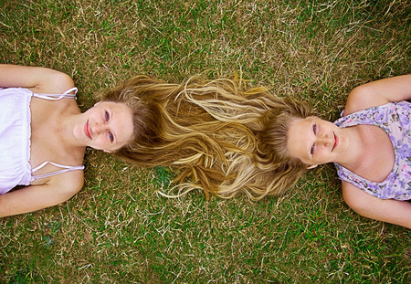 tangling: Girls lying in field,long hair entwined,overhead view LANG_EVOIMAGES