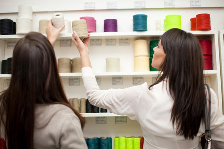 decide deciding: Women choosing spool of thread in store LANG_EVOIMAGES