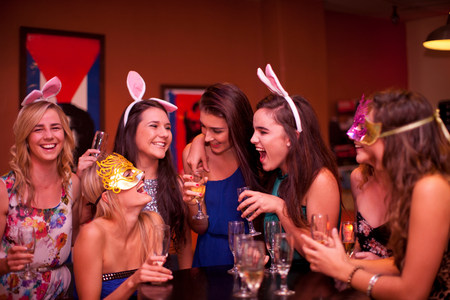 giggling: Young women laughing with drinks at hen party
