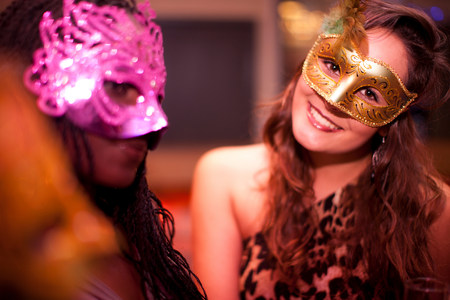 Young women wearing masquerade masks at hen party