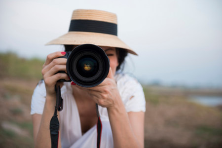 personal perspective: Woman wearing hat taking photograph