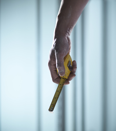Close up of hand holding measuring tape LANG_EVOIMAGES