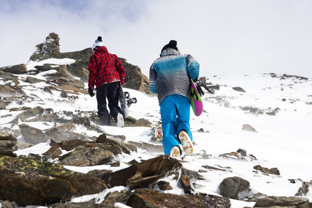 mountainous: Snowboarders hiking on rocky slope