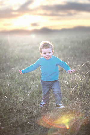 gratify: Toddler boy playing in grassy field