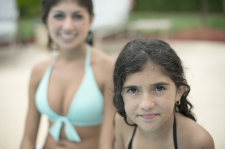 in twos: Sisters sitting by swimming pool