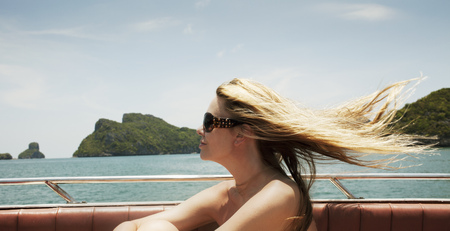 wind blown hair: Woman sitting in boat on lake LANG_EVOIMAGES