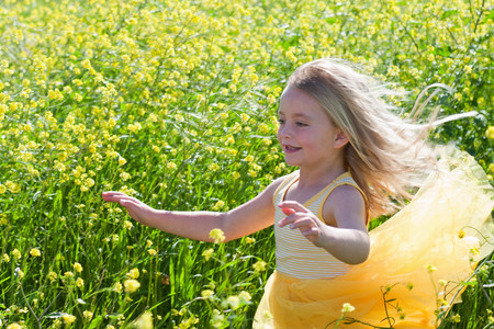 gratify: Smiling girl playing in field of flowers