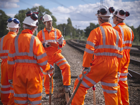 defended: Railway workers talking on train tracks