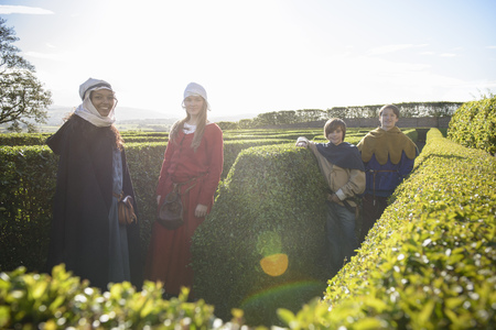 gratify: Students in period dress in hedge maze