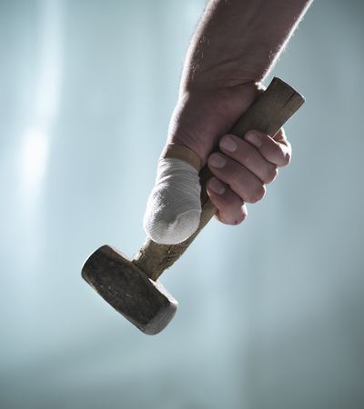 Close up of bandaged thumb and mallet