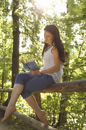 tomes: Woman reading book in forest