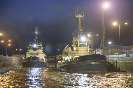 Remolcadores atracados en el puerto por la noche