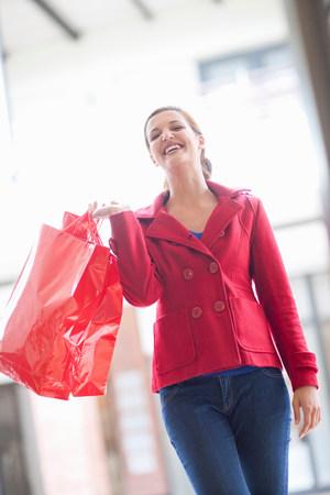 shopper: Happy young woman carrying shopping bags