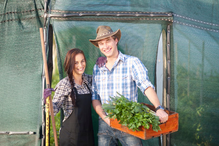 looking at viewer: Young woman and man with vegetables grown on farm