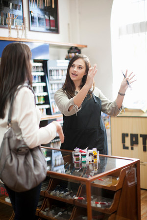 advice: Shop assistant talking to customer in craft shop LANG_EVOIMAGES
