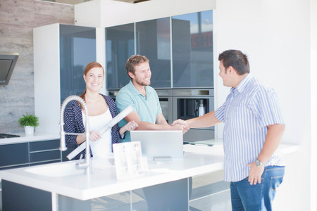 affable: Young couple with salesman in kitchen showroom