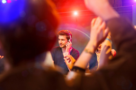 ear buds: Disc jockey surrounded by people dancing LANG_EVOIMAGES