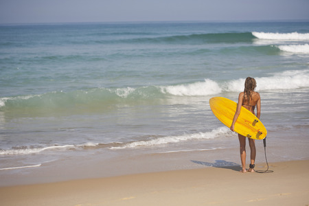 seascapes: Woman carrying surfboard on beach