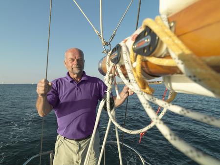 lake front: Man adjusting rigging on sailboat