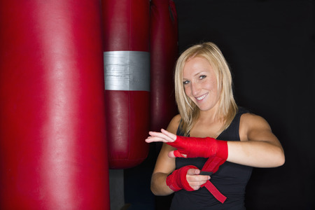 fastened: Boxer wrapping her hands in gym