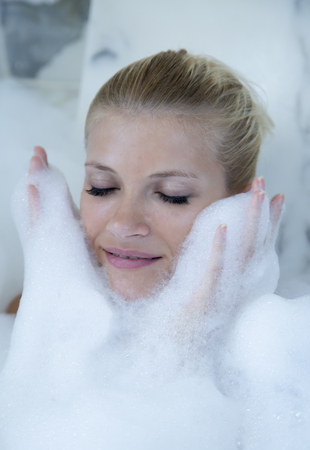Woman playing in bubble bath LANG_EVOIMAGES