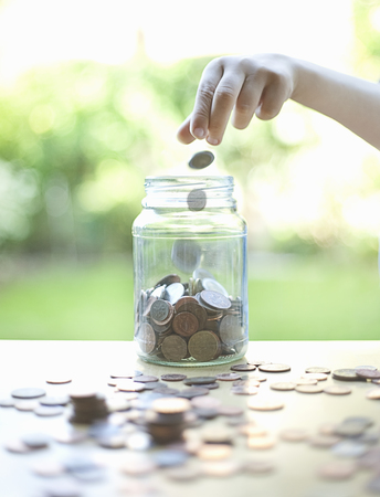 preadolescent: Hand tossing coins in change jar