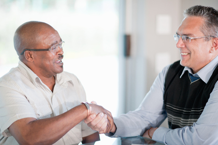 agrees: Businessmen shaking hands in meeting