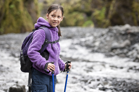 Girl hiking on rocky river