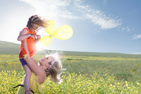 wind blown: Sisters playing in field of flowers