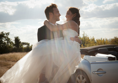 joyous: Newlywed groom carrying bride outdoors