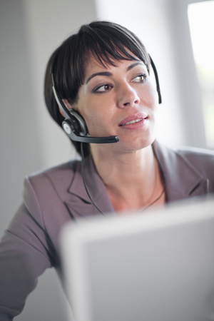 hands free device: Businesswoman wearing headset at desk