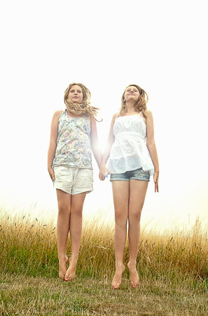 Girls in field,holding hands and jumping
