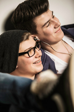 two persons only: Two teenage boys smiling and listening to earphones