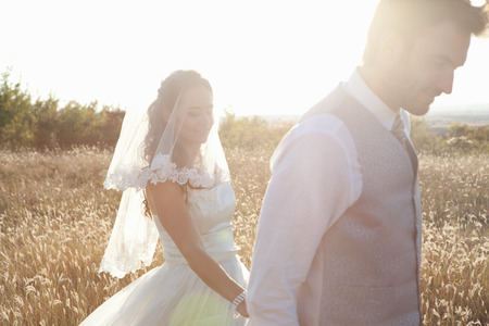 formals: Newlywed couple walking outdoors LANG_EVOIMAGES