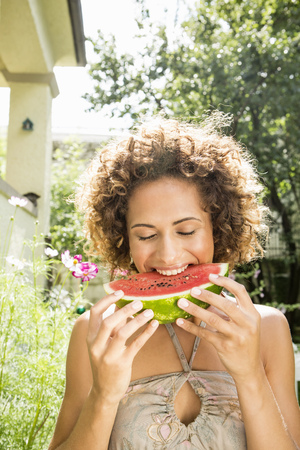 Smiling woman eating watermelon LANG_EVOIMAGES