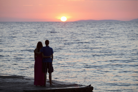 sweethearts: Couple watching sunset on pier