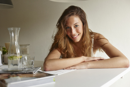 gratify: Smiling woman leaning on table
