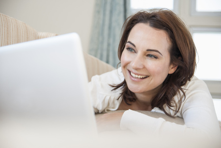 gratify: Smiling woman using laptop on sofa