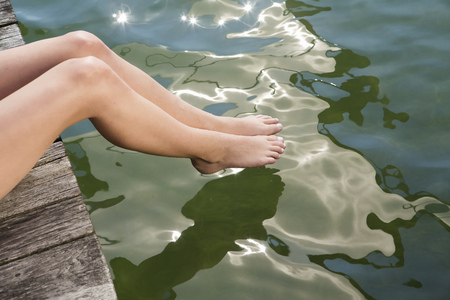 Woman dipping toes into still lake