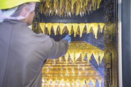 ahorcada: Trabajador fumando filetes de eglefino en la fábrica LANG_EVOIMAGES