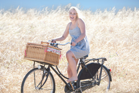 frock: Woman riding bicycle in tall grass