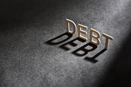 shadowed: Letters spelling 'debt casting shadow