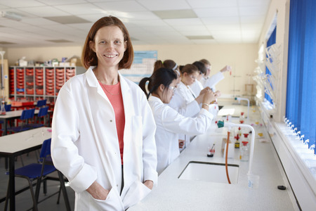 posed: Teacher with students in chemistry lab LANG_EVOIMAGES