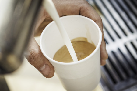 Close up of milk pouring into coffee cup LANG_EVOIMAGES